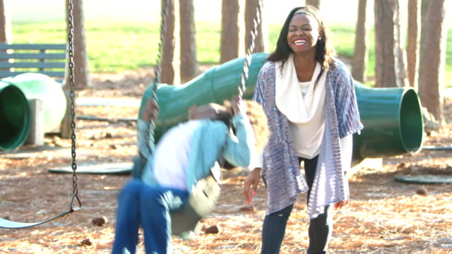 african-american mother and daughter on playground swing - single mother stock videos & royalty-free footage