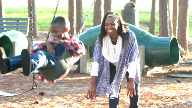 african-american mother and son on playground swing - swing stock videos and b-roll footage