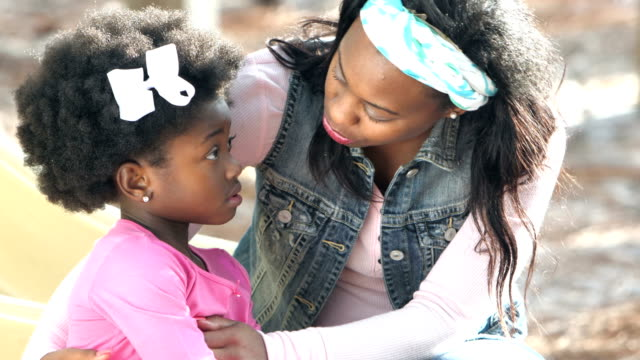 African-American mother consoling little girl