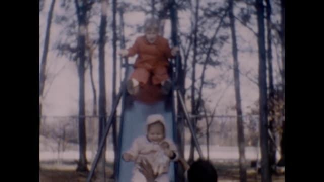 1958 African-American Nanny Helping Sisters on Slide