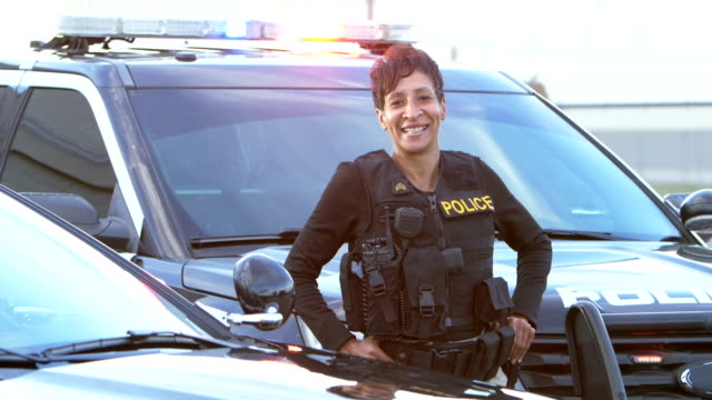 african-american policewoman standing by patrol car - police force stock videos & royalty-free footage