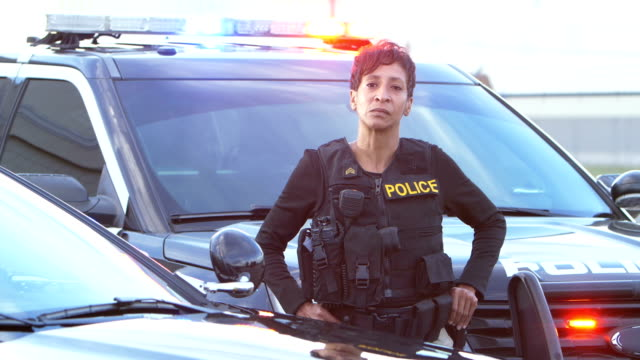 african-american policewoman standing by patrol car - police woman stock videos & royalty-free footage
