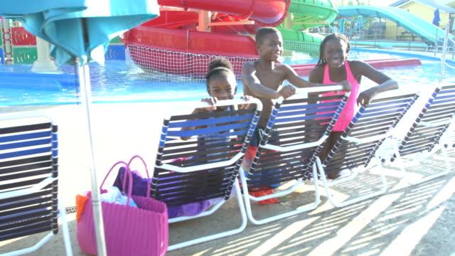 stockvideo's en b-roll-footage met afro-amerikaanse broers en zussen op waterpark op lounge stoelen - 6 7 years