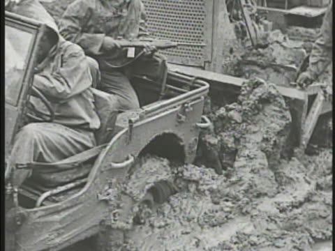 africanamerican soldier driving jeep in mud w/ bulldozer pushing behind us soldiers crossing swollen river us soldiers carrying supplies through mud... - 四輪駆動車点の映像素材/bロール
