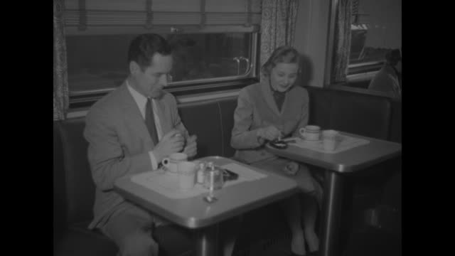 vidéos et rushes de african-american steward delivers tray of coffees to table of white men / vs white male offers white female at table next to his a cigarette and then... - pennsylvanie