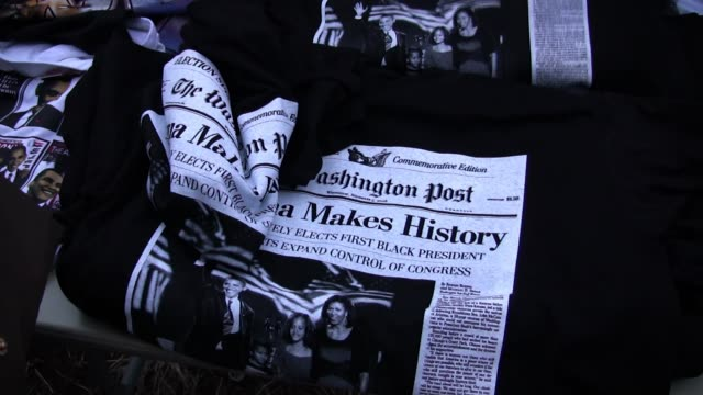"africanamerican street vendors sell tshirts features a washington post front pages reading ""obama makes history us decisively elects first black... - アメリカ黒人の歴史点の映像素材/bロール"