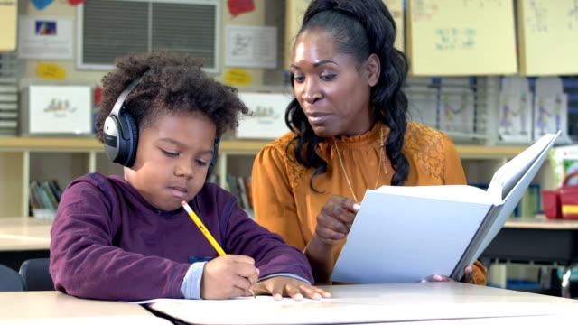 vídeos de stock, filmes e b-roll de professor africano-americano e estudante da escola primária - protetor de ouvido