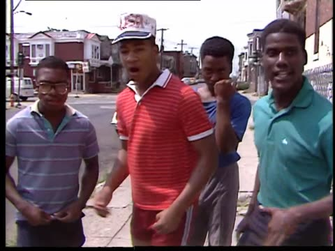 4 AfricanAmerican teenage boys rapping with human beat boxer solo on sidewalk
