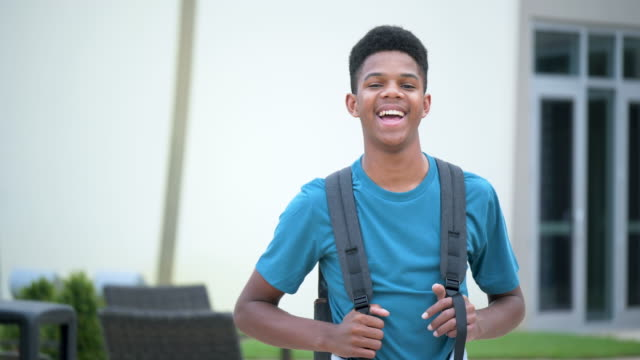 vídeos de stock e filmes b-roll de african-american teenager standing outside school - 14 15 years