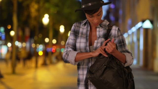 African-American tourist on Champs-Elysees in Paris puts phone away in purse