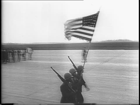 AfricanAmerican troops parade to camera with helmets guns American flag / trucks pass with antiaircraft weapons / Sergeant Joe Louis exits plane and...