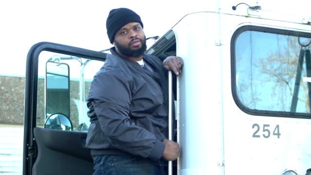 アフリカ系アメリカ人のトラック運転手、セミトラックに乗り込む - トラック運転手点の映像素材/bロール