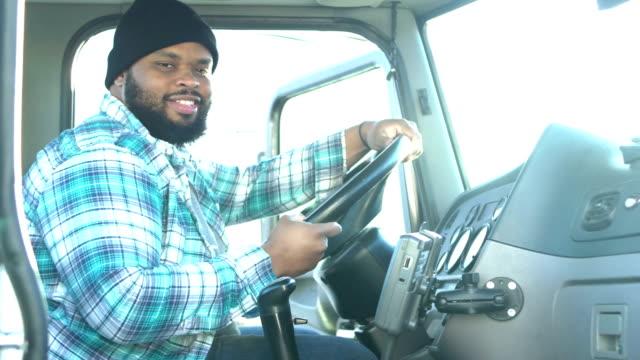 アフリカ系アメリカ人のトラック運転手、セミトラックに登る - トラック運転手点の映像素材/bロール