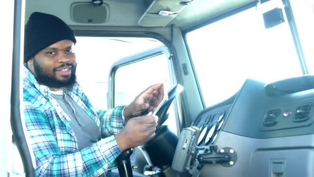 african-american truck driver using digital tablet - trasporto merci via terra video stock e b–roll