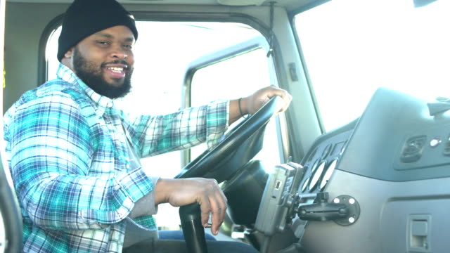 african-american trucker in driver's seat of semi-truck - woolly hat stock videos & royalty-free footage