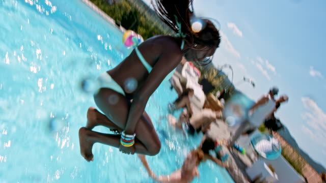 SLO MO African-American woman and a Caucasian man jumping into the pool at the party one after another