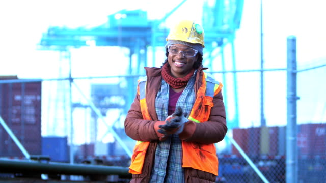African-American woman at shipping port, rubbing hands