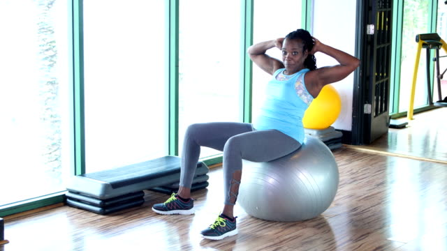 african-american woman doing sit-ups on fitness ball - pallone per fitness video stock e b–roll
