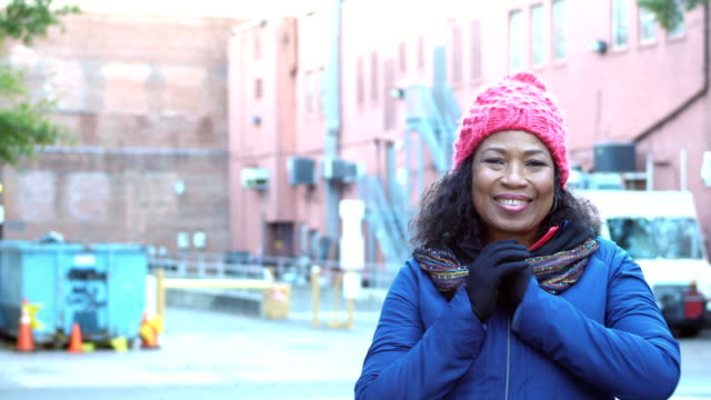 african-american woman in city with knit hat, scarf - hands clasped stock videos and b-roll footage