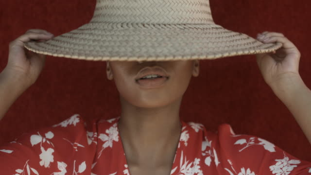 vídeos de stock, filmes e b-roll de african-american woman lifts up hat, close up - exterior