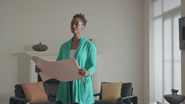 vídeos de stock e filmes b-roll de african-american woman looks at home design plans indoors - arquiteta