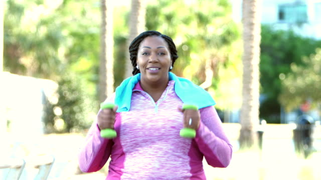 African-American woman power walking in park