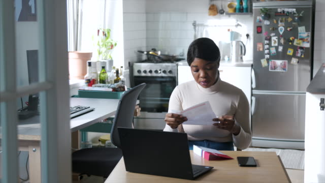 african-american woman reading mail-in voting ballot at home during usa presidential election - mail stock videos & royalty-free footage