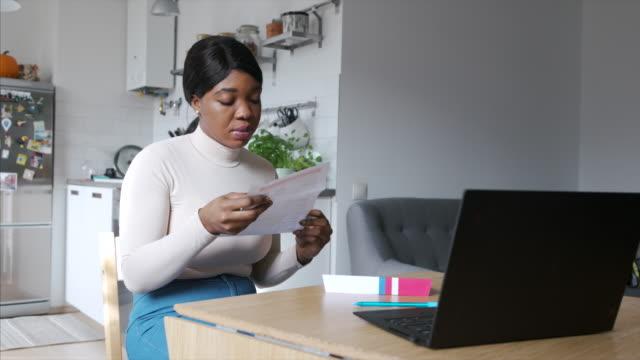 afroamerikanische frau liest brief-in-wahl zu hause während der us-präsidentschaftswahl - wahlschein stock-videos und b-roll-filmmaterial