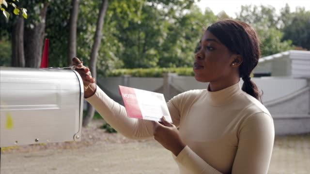 vídeos de stock e filmes b-roll de african-american woman receiving mail-in voting ballot during usa presidential election - eleições
