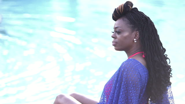 african-american woman sitting by swimming pool - shoulder stock videos and b-roll footage