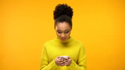 African-American woman using smartphone, excited about job acceptance e-mail