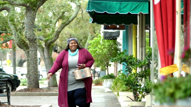 african-american woman walking by storefronts - plus size model stock videos & royalty-free footage