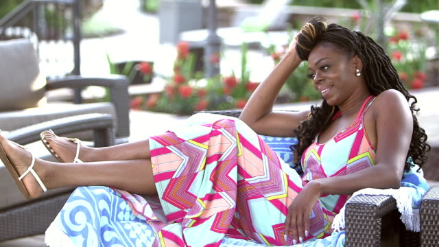 african-american woman walks up and relaxes on patio chair - armchair stock videos & royalty-free footage