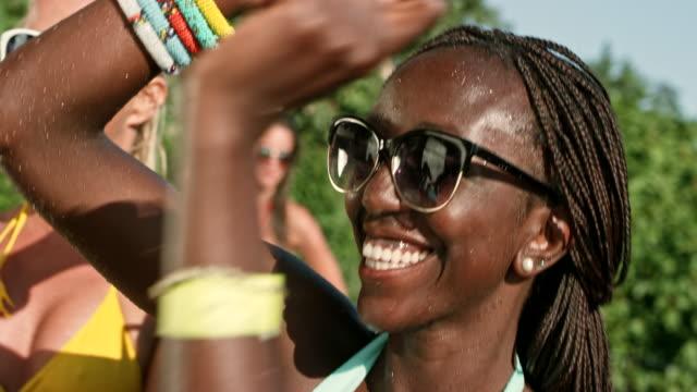 vidéos et rushes de slo mo afro-américaine lunettes de soleil dansant dans son maillot de bain lors d'une soirée piscine - d'origine africaine