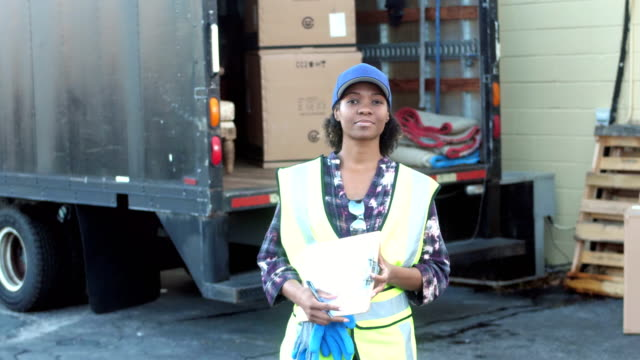 African-American woman with delivery truck writing on clipboard