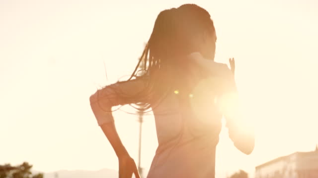 SLO MO TS African-American woman with long braided hair running in sunny stadium with sunset flares