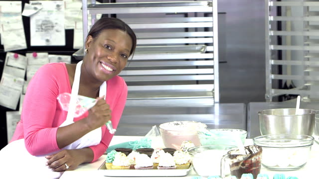 african-american woman working in a bakery kitchen - forno video stock e b–roll