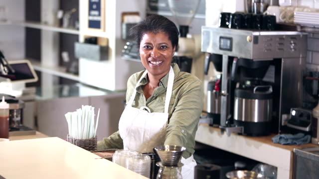 stockvideo's en b-roll-footage met afro-amerikaanse vrouw die in een coffeeshop werkt - alleen één oudere vrouw
