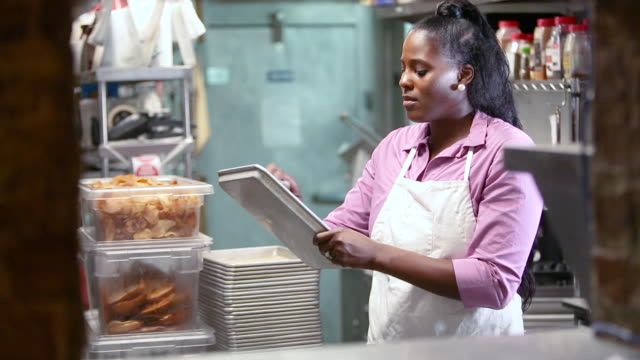 african-american woman working in restaurant kitchen - baking tray stock videos & royalty-free footage