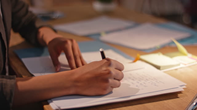 african-american woman writing notes in her notebook behind her office desk - adhesive note stock videos & royalty-free footage