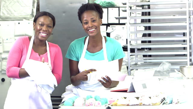 african-american women in a bakery kitchen, paying bills - forno video stock e b–roll