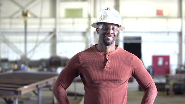 African-American worker in factory, walks up to camera