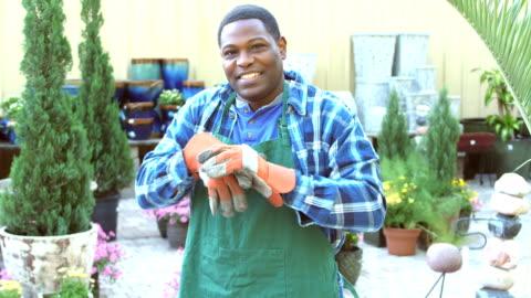 vidéos et rushes de travailleur afro-américaine en pépinière met des gants - porte structure créée par l'homme