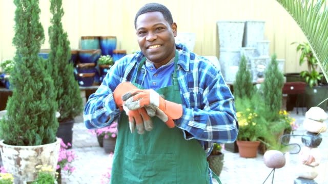 vidéos et rushes de travailleur afro-américaine en pépinière met des gants - porter