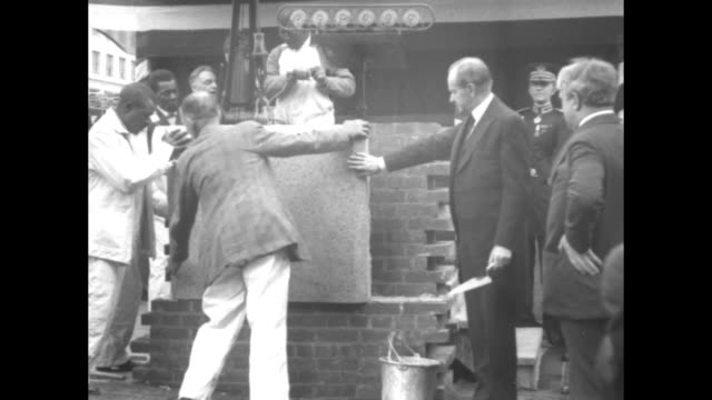 AfricanAmerican workers set up cornerstone for new National Press Club President Calvin Coolidge stands by with trowel / Coolidge speaks at podium...