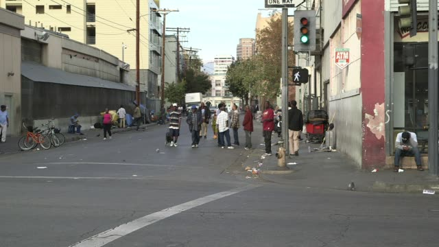african-americans chatting, walking on streets of people laying on streets with their belongings - crisi video stock e b–roll