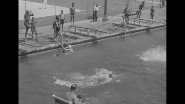 african-americans jump off diving board into swimming pool, joining swimmers having fun below; young man in foreground does a backward somersault;... - sunbathing stock videos & royalty-free footage