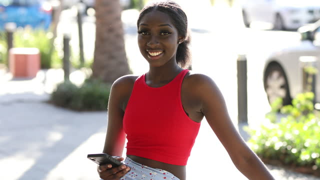 african-australian girl in red top using mobile phone outdoors - video portrait stock videos & royalty-free footage