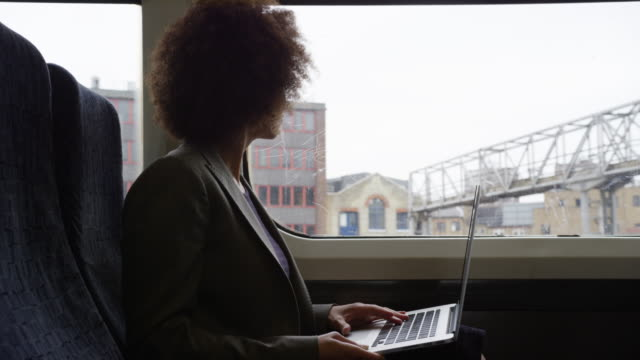stockvideo's en b-roll-footage met afro american businesswoman working on laptop whilst on her commute - profiel