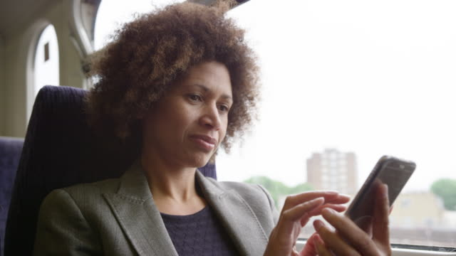 stockvideo's en b-roll-footage met afro american commuter on her way to work looking at smart phone - one mid adult woman only